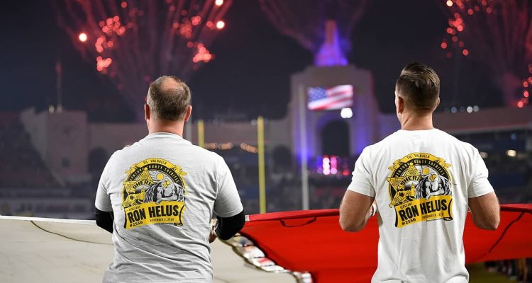Photo of first responders holding the flag at the Los Angeles Rams game