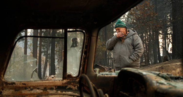 Photo of a wildfire victim wiping his eyes as he walks by a burned car