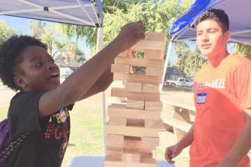 Photo of two teens playing giant Jenga in a Fresno park