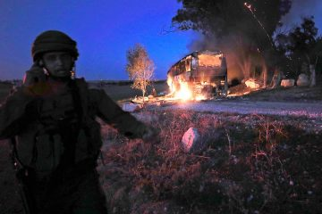 Photo of an Israeli soldier standing next to a burning bus