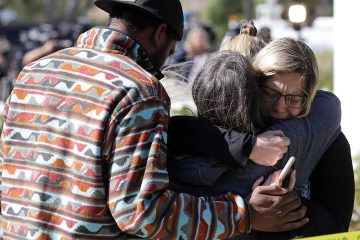 Photo of mourners embracing out side of the Thousand Oaks Teen Center