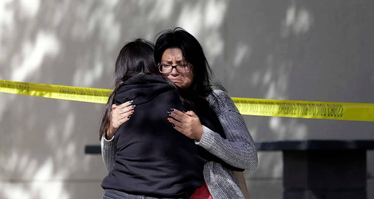 Photo of mourners embracing outside the Thousand Oaks Teen Center