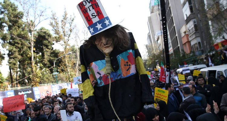 """Photo of """"Uncle Sam"""" being held up by demonstrators during a rally in Iran"""
