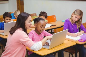 Shutterstock photo of teacher with young math students at their desks