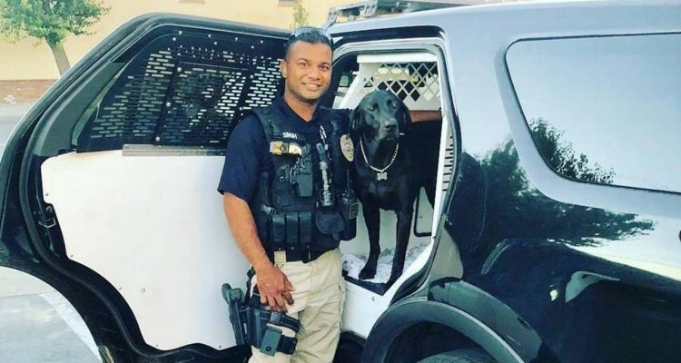 Photo of Newman, California, police officer Ronil Singh standing next to his patrol car