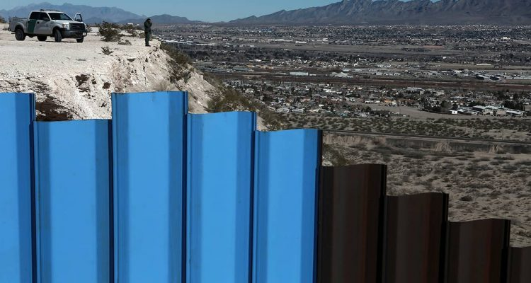 Photo of border fence and border patrol agent in New Mexico