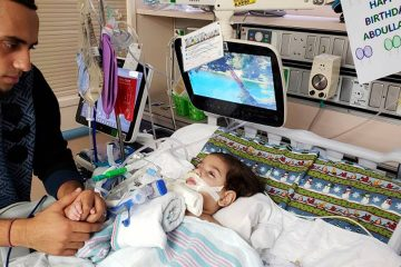 Photo of Ali Hassan with his dying 2-year-old son Abdullah