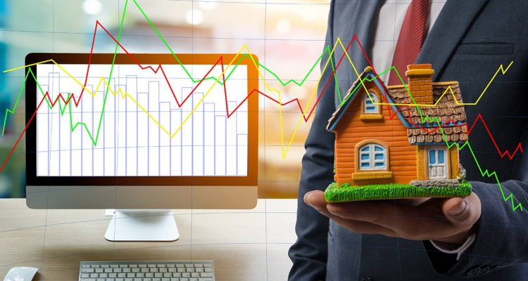 Photo of man holding a house next to a computer with stock charts