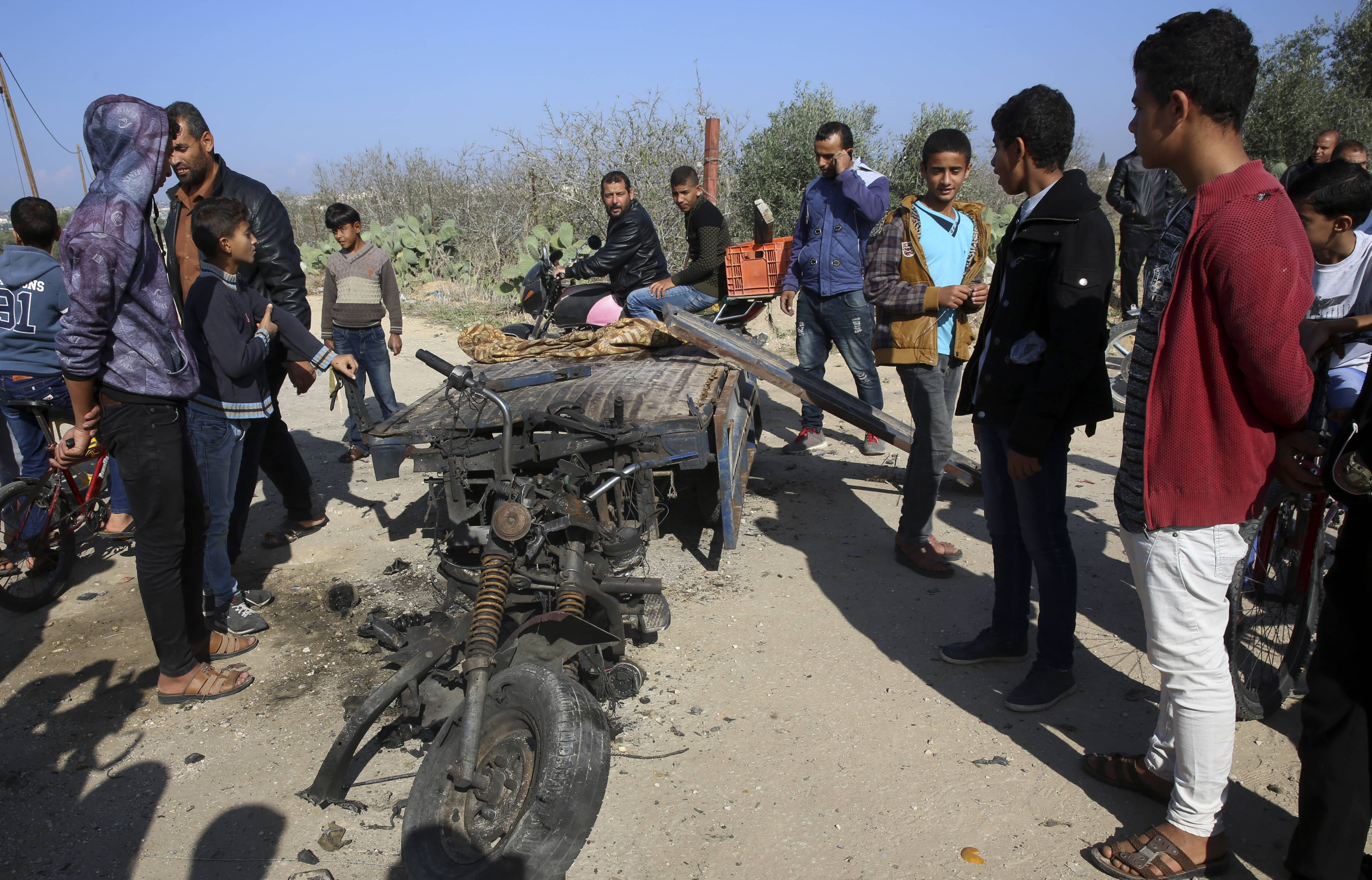 Photo of Palestinians inspecting a vehicle that was destroyed