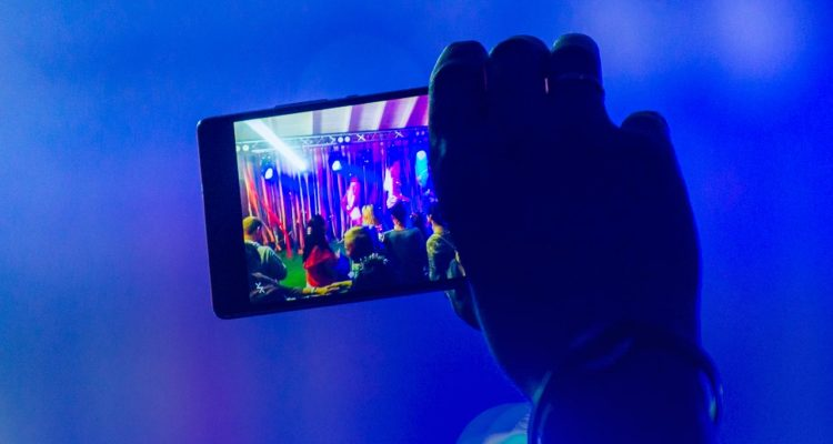 Photo of a parent videoing a school musical with a smart phone