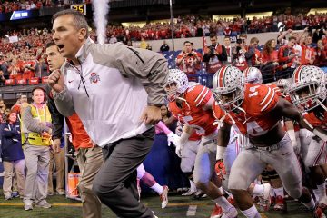 Photo of Urban Meyer running onto the field with his team