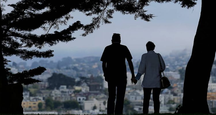 Photo of a man and woman walking under trees in San Francisco