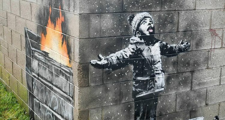 Photo of mural by Banksy on the side of a garage