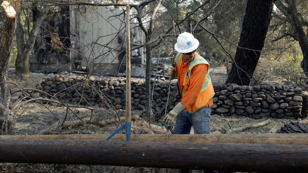 Photo of PG&E employee replacing power poles damaged by a wildfire