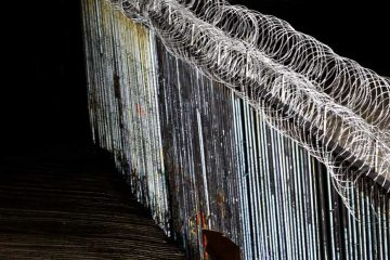 Photo of a boy looking at the border wall topped with razor wire