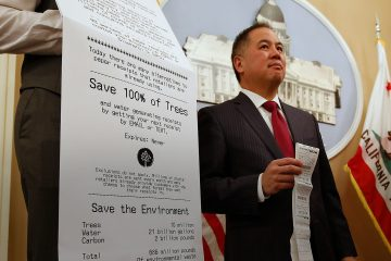 Photo of Assemblyman Phil Ting of San Francisco with a long paper receipt