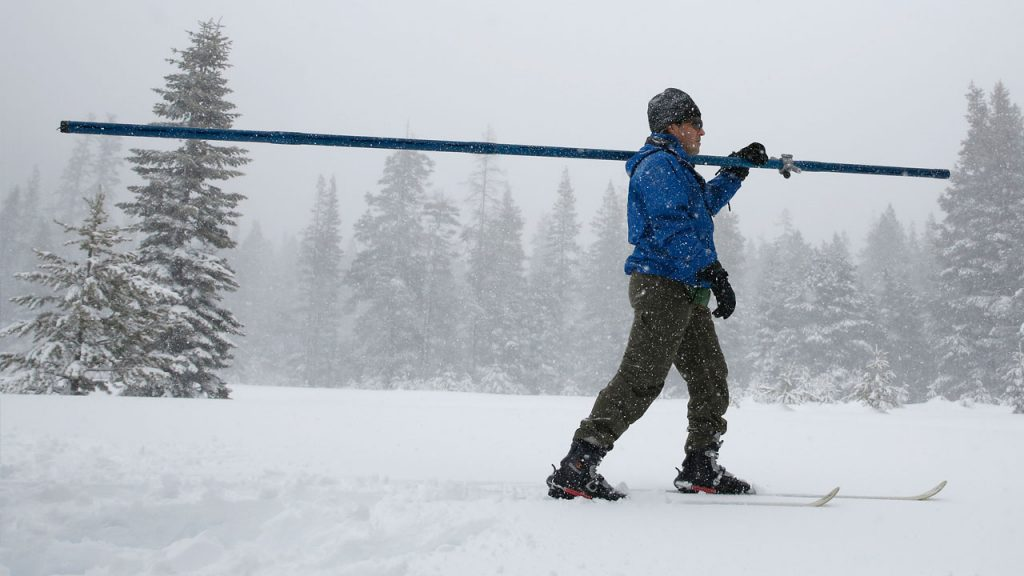 Photo of man carrying snow measuring equipment