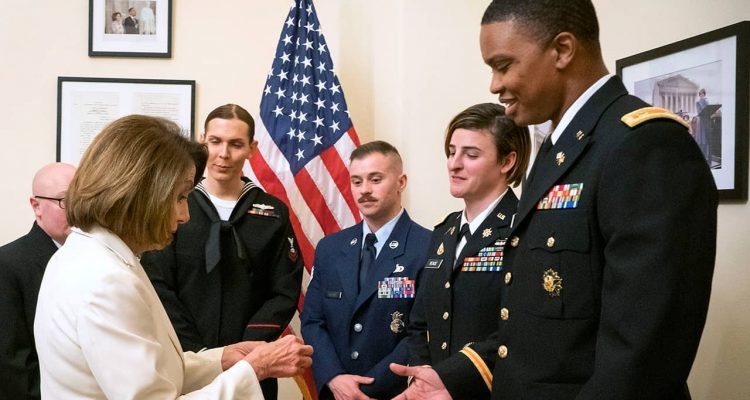 Photo of Nancy Pelosi giving challenge coins to military service members