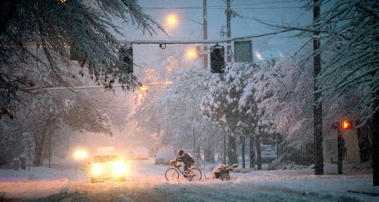 Photo of man riding a bicycle through the snow in Oregon