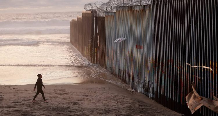 Photo of a woman walking along the beach next to the border wall in Mexico