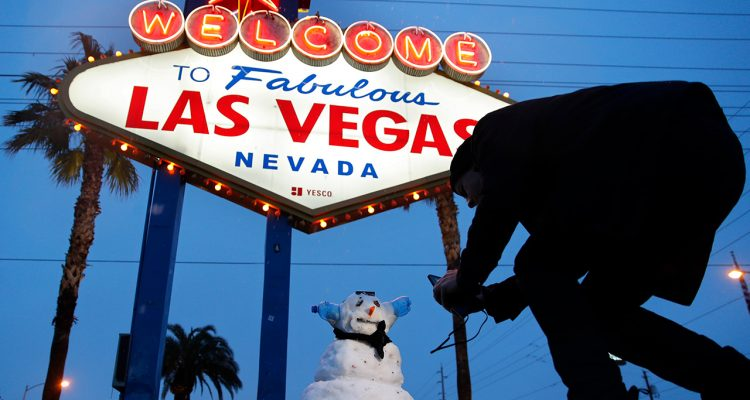 """Photo of a snowman near the """"Welcome to Las Vegas"""" sign"""