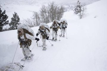 Photo of US Marines walking along a snow-covered trail
