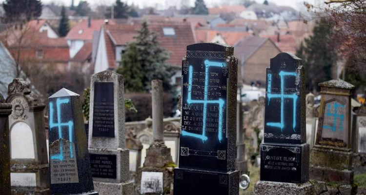 Photo of gravestones vandalized with swastikas