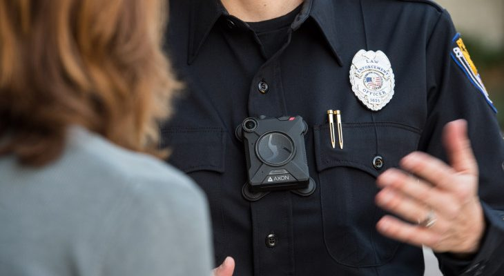 Photo of an officer with a body cam talking to a woman