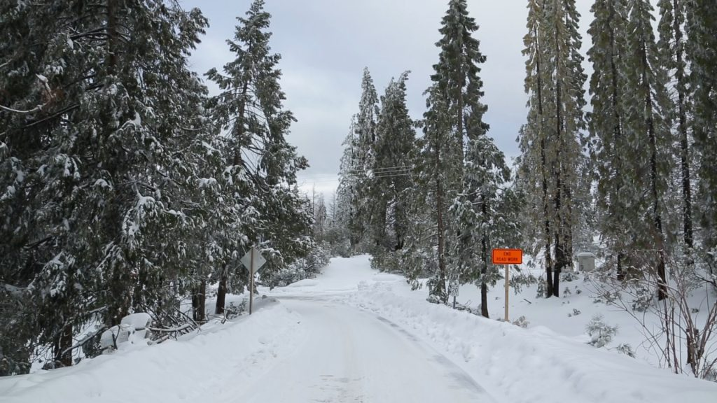 A photo of snow covering the road into Shaver Lake