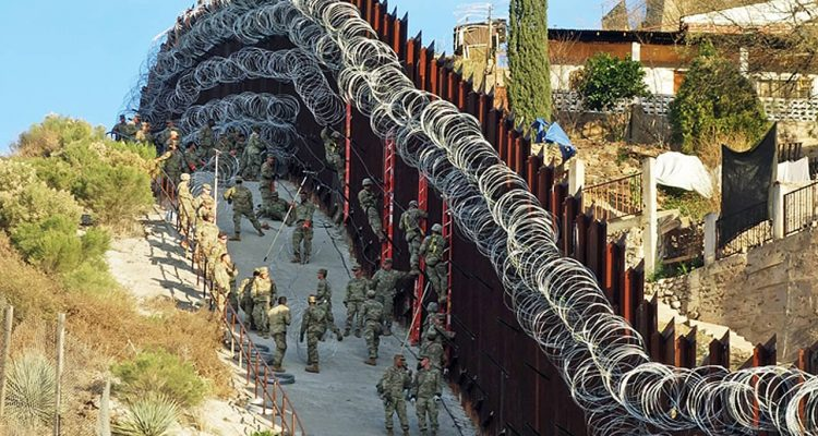 Photo of border wall in Arizona covered in razor wire