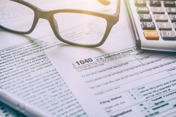 Photo of tax form, glasses, and a calculator