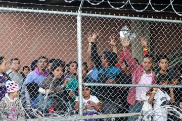 Photo of migrant families behind a barbed wire fence