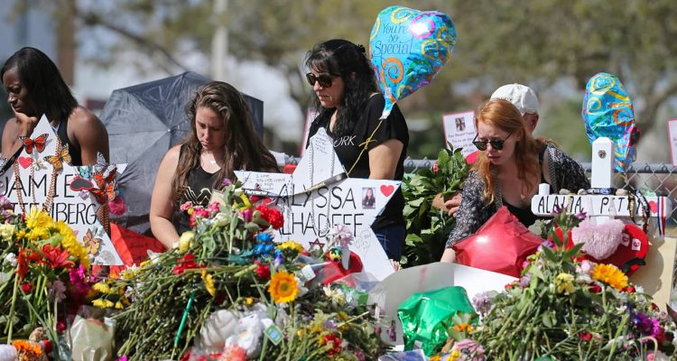 Photo of mourners paying tribute at a memorial for the victims of the shooting at Marjory Stoneman Douglas High School