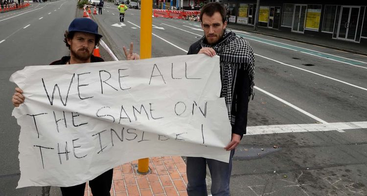 Photo of Linwood mosque shooting survivor Elliot Dawson, right, and a friend Shay Kenny holding a sign at an intersection