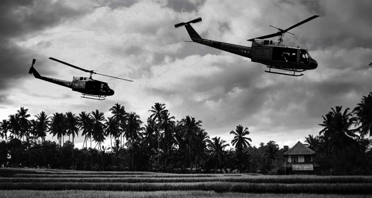 Photo of Vietnam War 'style' B&W image circa 1968 of two helicopters flying low over the rice paddies of South Vietnam looking for Viet Cong insurgents during the Tet Offensive in 1968.