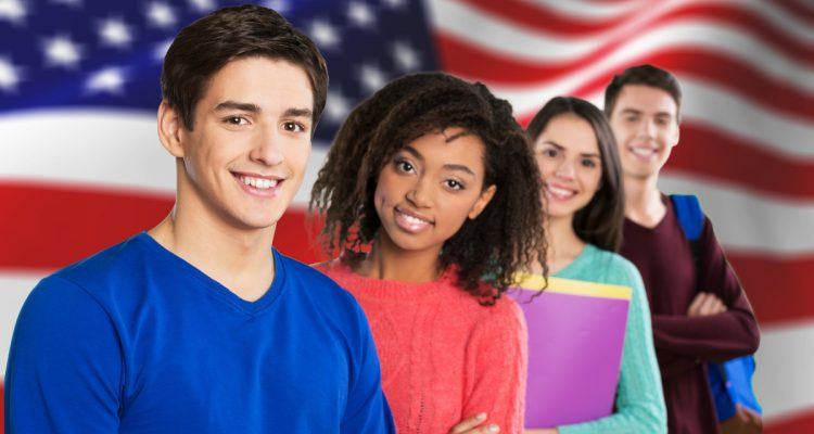 Photo of students posing in front of an American flag