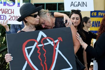 Leslie Gollub, left, and Gretchen Gordon hug at a vigil held to support the victims of the Chabad of Poway synagogue