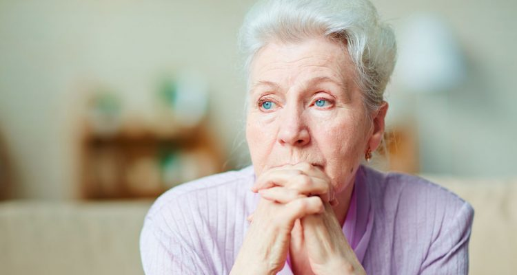 Older woman gazes off into the distance.
