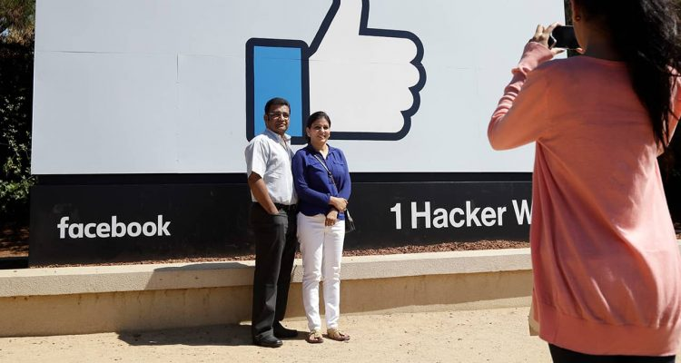 Photo of visitors taking pictures in front of the Facebook logo