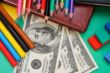 Photo of school supplies and hundred dollar bills