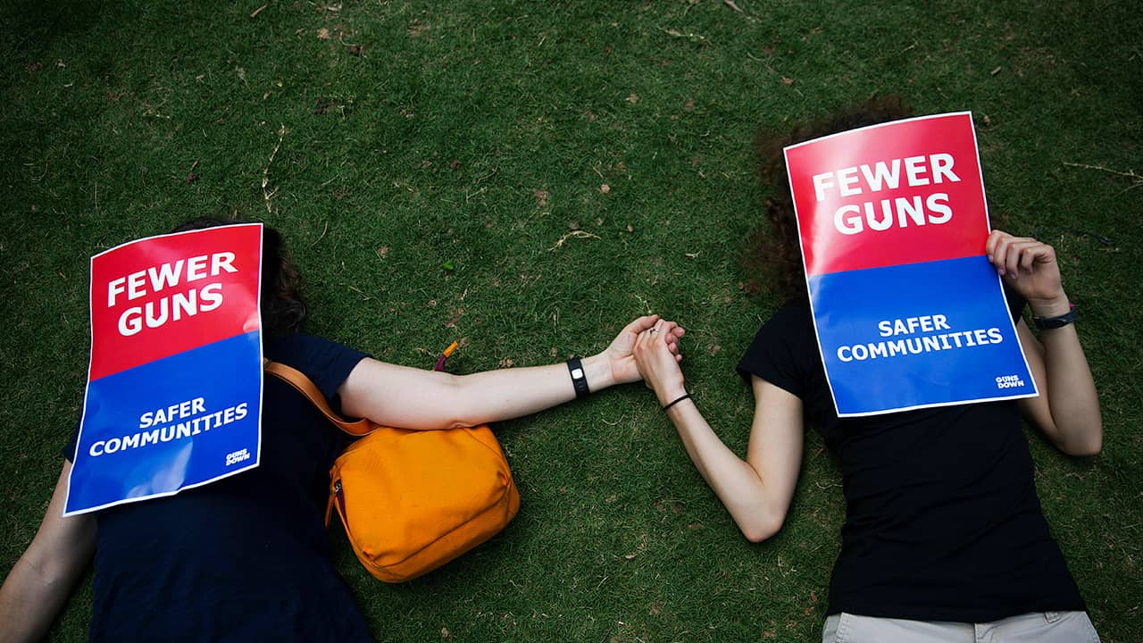 Photo of demonstrators holding hands at the NRA convention