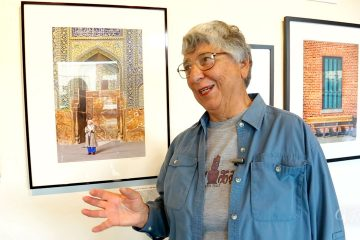 Photographer Helen Gigliotti stands next to a photo from her trip to Iran.