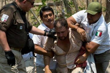 Photo of a Central American migrant being detained by Mexican immigration agents in Mexico