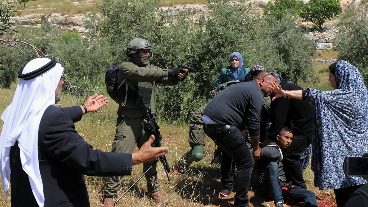 Photo of an Israeli soldier pointing his pistol at a group of Palestinians