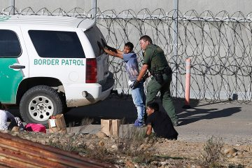 Photo of asylum seeker being taken into custody by US Border Patrol