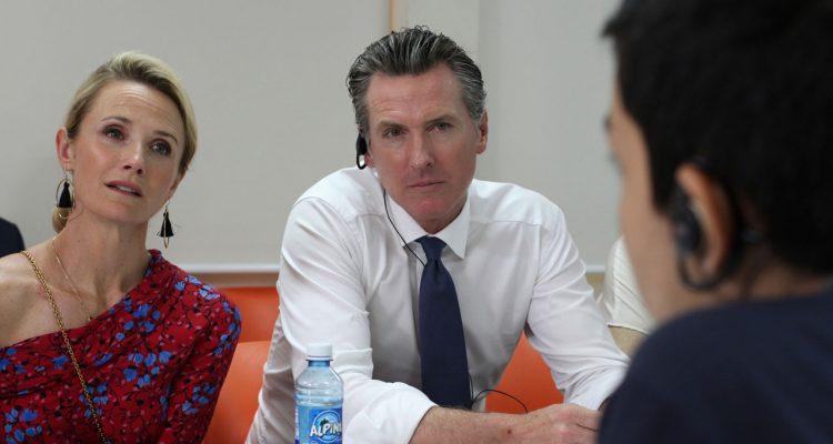Gov. Gavin Newsom and his wife, Jennifer Siebel Newsom talk with migrant in El Salvador.