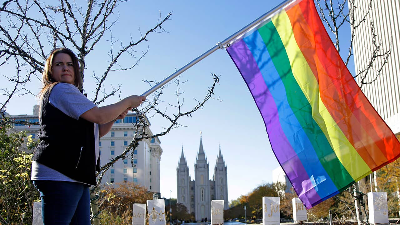 Photo of a woman holding a rainbow flag