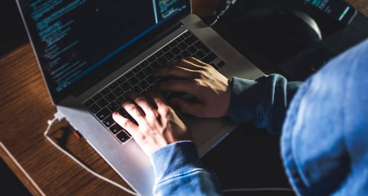 Concept photo of identity theft showing a hacker at a keyboard