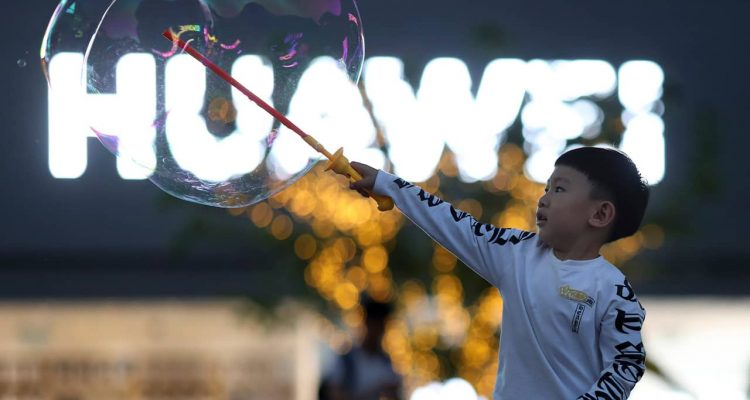 Photo of a child playing with bubbles near the Huawei logo