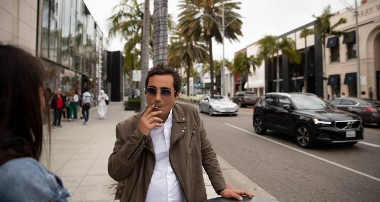 Photo of of man smoking in front of luxury shops in Beverly Hills